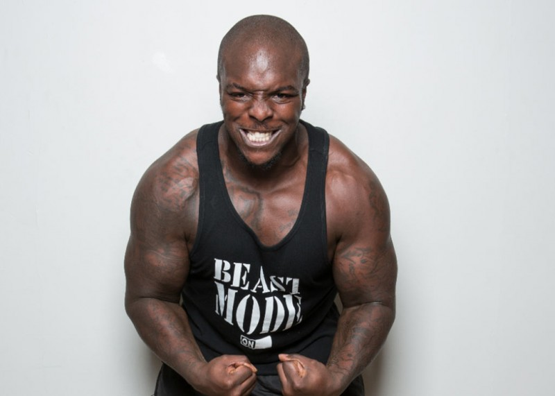 Adebayo Akinfenwa showing off his muscles and strength