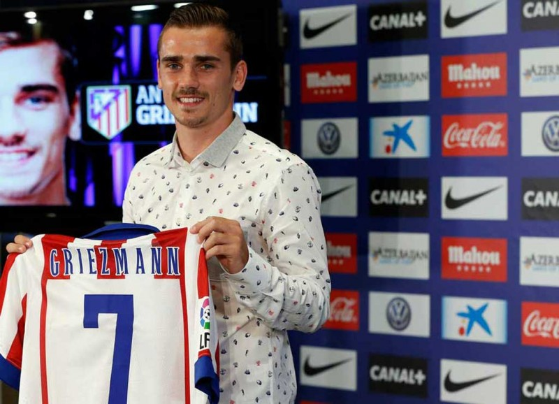 Antoine Griezmann holding his new Atletico Madrid jersey