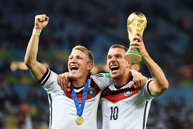 Bastian Schweinsteiger and Podolski, holding the World Cup trophy