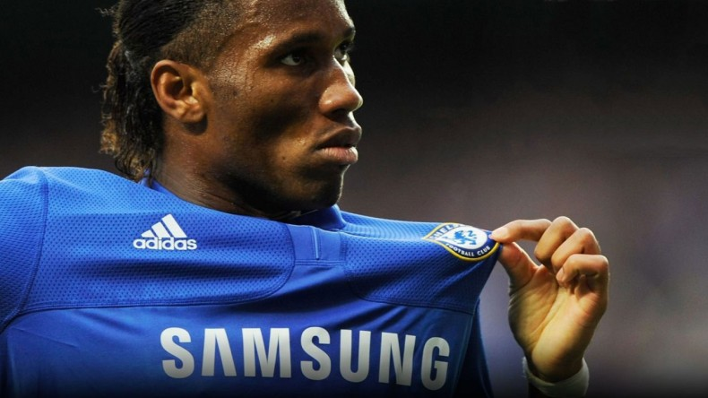 Didier Drogba holding Chelsea's badge on his jersey