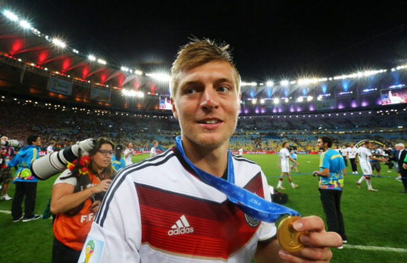 Toni Kroos holding his World Cup medal